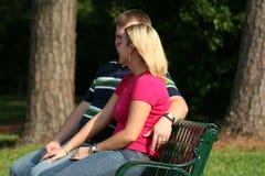 Couples sur un banc de stationnement Photographie stock libre de droits