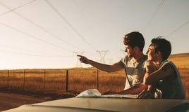 Couples sur un voyage par la route regardant la carte pour la navigation Photographie stock libre de droits