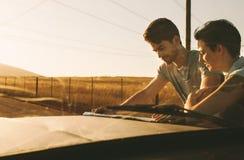 Couples sur un voyage par la route regardant la carte pour la navigation Image libre de droits