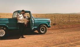 Couples sur un voyage par la route regardant la carte pour la navigation Photos libres de droits