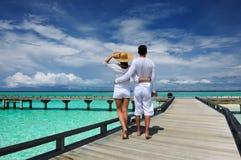 Couples sur une jetée de plage chez les Maldives Photo stock