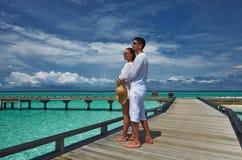 Couples sur une jetée de plage chez les Maldives Photographie stock