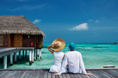 Couples sur une jetée de plage chez les Maldives Photos stock