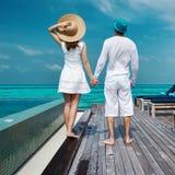 Couples sur une jetée de plage chez les Maldives Photographie stock libre de droits