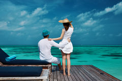 Couples sur une jetée de plage chez les Maldives Images stock