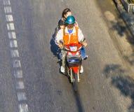 Couples sur une motocyclette sur la route à Bangkok Image stock