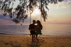 Couples sur une oscillation contre du coucher du soleil Photographie stock libre de droits