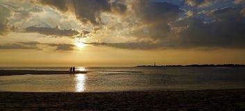 Couples sur une plage au coucher du soleil Photographie stock