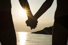 Couples sur une plage tenant des mains au coucher du soleil Photo stock