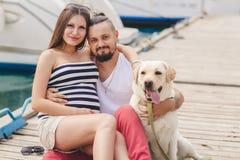 Couples sur une promenade dans le port avec un chien image stock
