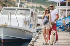 Couples sur une promenade dans le port avec un chien photo libre de droits