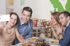 Couples taking selfie in restaurant Royalty Free Stock Images