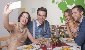 Couples taking selfie in restaurant Stock Image