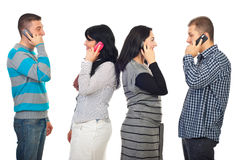 Couples talking by phone mobiles. Two couples talking by phone mobiles and each of them standing in profile  isolated on white background Royalty Free Stock Photography