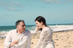 Couples talking and sitting on the beach Stock Image