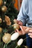 Couples tenant des babioles accrochant sur l'arbre de Noël Image libre de droits