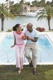 Couples tenant des cocktails tout en se penchant sur la rampe de piscine Image libre de droits