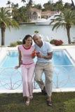 Couples tenant des cocktails tout en se penchant sur la rampe de piscine Photo stock