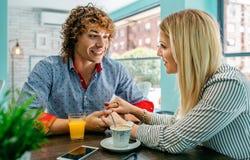 Couples tenant des mains à un café Photos libres de droits