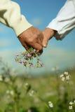 Couples tenant des mains avec des fleurs photos libres de droits