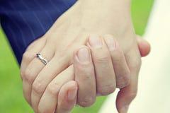 Couples tenant des mains avec l'anneau de mariage Photographie stock
