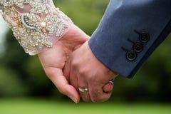 Couples tenant des mains avec le fond naturel vert Images libres de droits