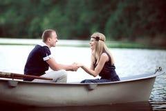 Couples tenant des mains dans le bateau Photos libres de droits