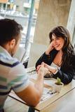 Couples tenant des mains dans le restaurant et le sourire Photographie stock