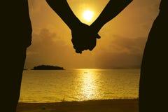 Couples tenant des mains et le beau coucher du soleil Image libre de droits