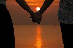 Couples tenant des mains et le beau coucher du soleil trouble Image stock