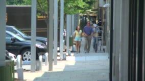 Couples tenant des mains tout en marchant le long des devanture de magasin banque de vidéos