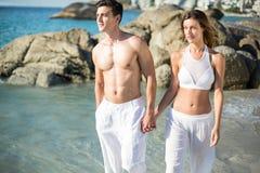 Couples tenant des mains tout en marchant sur le rivage Images libres de droits