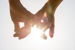 Couples tenant des mains vers le soleil Images stock