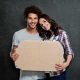 Couples tenant la bannière de carton Photographie stock