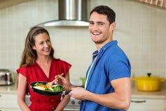 Couples tenant la casserole de légumes et de sourire Images stock