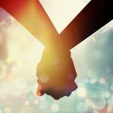 Couples tenant la main à la hausse du soleil Image stock