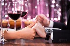 Couples tenant la main de chacun au dîner Photo stock
