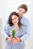 Couples tenant la pousse verte à la maison Image stock