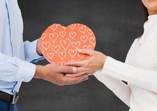 Couples tenant le boîte-cadeau en forme de coeur Images stock