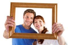 Couples tenant le cadre en avant de eux Photos stock
