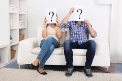 Couples tenant le signe de point d'interrogation devant le visage photographie stock libre de droits