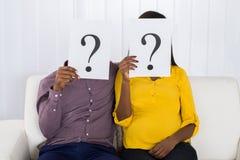 Couples tenant le signe de point d'interrogation devant le visage photos stock