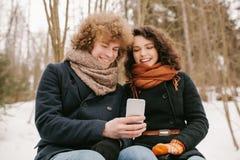 Couples tenant le smartphone se reposant dehors en hiver Photographie stock