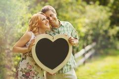Couples tenant le tableau en forme de coeur Image stock