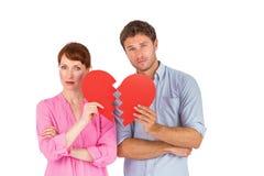 Couples tenant un coeur brisé Photographie stock libre de droits