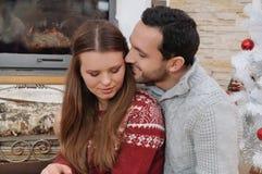 Couples tendres de jeunes dans des chandails confortables se reposant près de la cheminée dedans Image stock