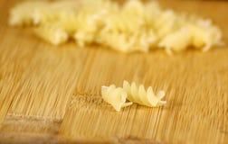 Couples tordus de pâtes sur le bureau en bambou Image stock
