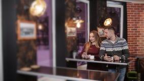 Couples tranquilles se reposant dans le restaurant et à l'aide des smartphones banque de vidéos