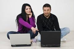 Couples travaillant à la maison d'ordinateur portatif Image libre de droits