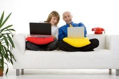 Couples travaillant sur des ordinateurs portatifs Photographie stock